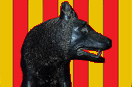 [image ALT: The head and neck of the Capitoline Wolf, seen in right profile, against a field of nine vertical stripes, the heraldic arms of Catalunya. The image serves as the icon on this site for José Balari y Jovany's 'Influencia de la Civilización Romana en Cataluña'.]
