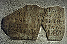 [image ALT: A fragmentary Roman inscription set in a wall.]